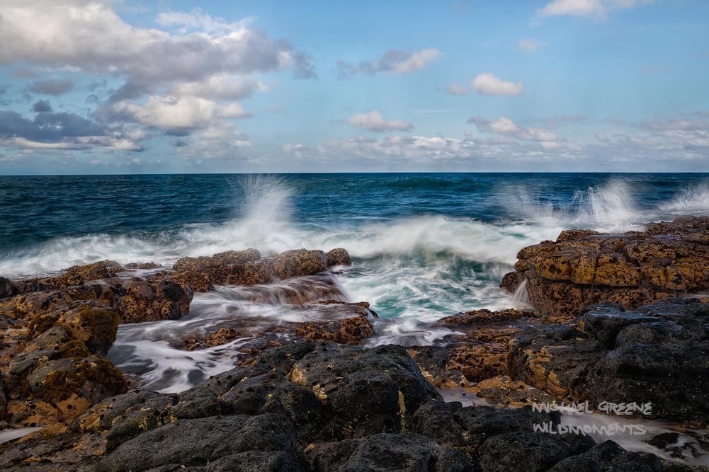 A rocky jetty bears the full force of the ocean wavesnear the coastal city of Kapaa, Hawaii.