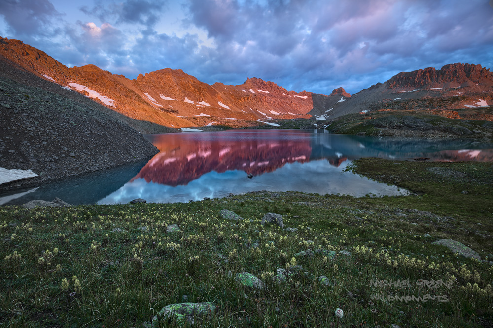 Colorful alpenglow reflects off of teal blue water during a summer's dawn at Columbine Lake. This hiking trail is located near...