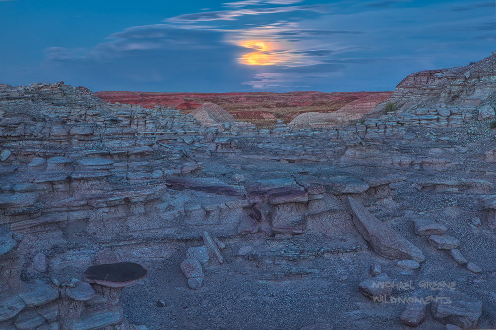 The full moon appears from behind a thick veil of clouds above the painted desert in the black forest area of Petrified Forest...