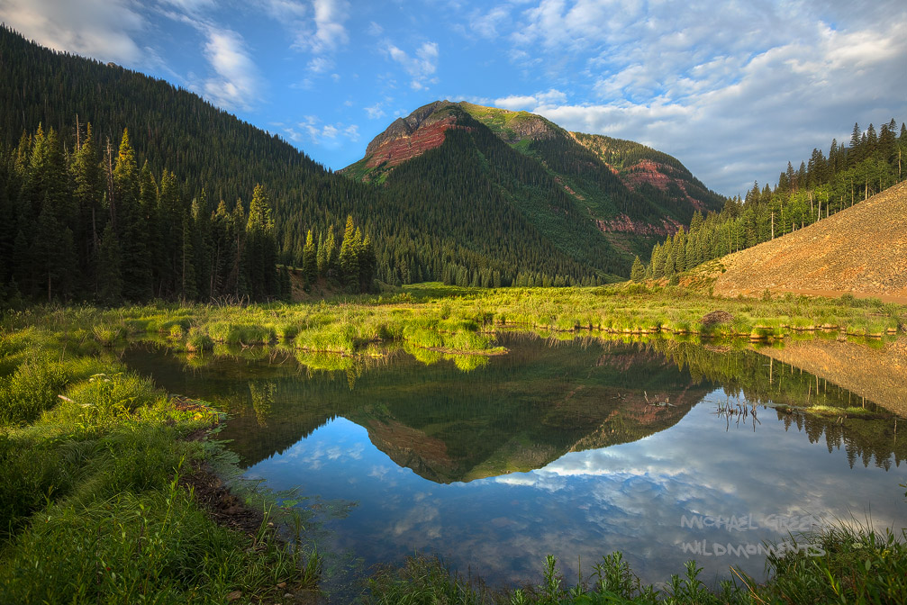 An unnamed red peak reflects perfectly in a tarn during the early morning near Ice Lake Basin Trail (Silverton, Colorado).