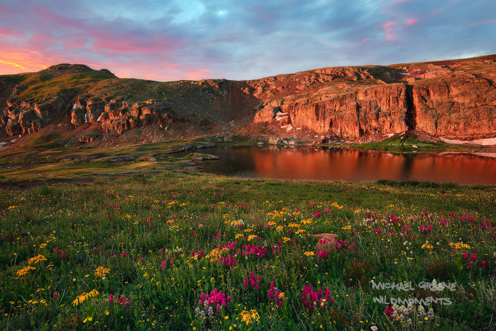 Alpenglow around sunrise on a stormy summer morning at Bullion King Lake in Porphyry Basin near the Red Mountain. The wildflower...