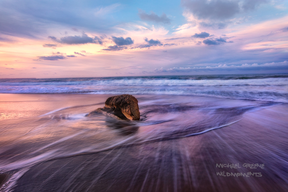A sandstone curiosity is circled by swirling surf at sunset on a beautiful summer evening at the Playa Negra. This beach is located...