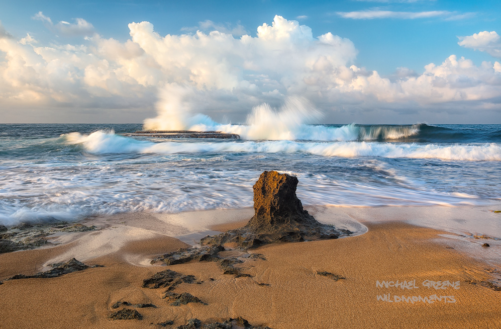 A lone sandstone formation decorates the beach near a rocky platform amid exploding Caribbean surf and dramatic clouds. This...