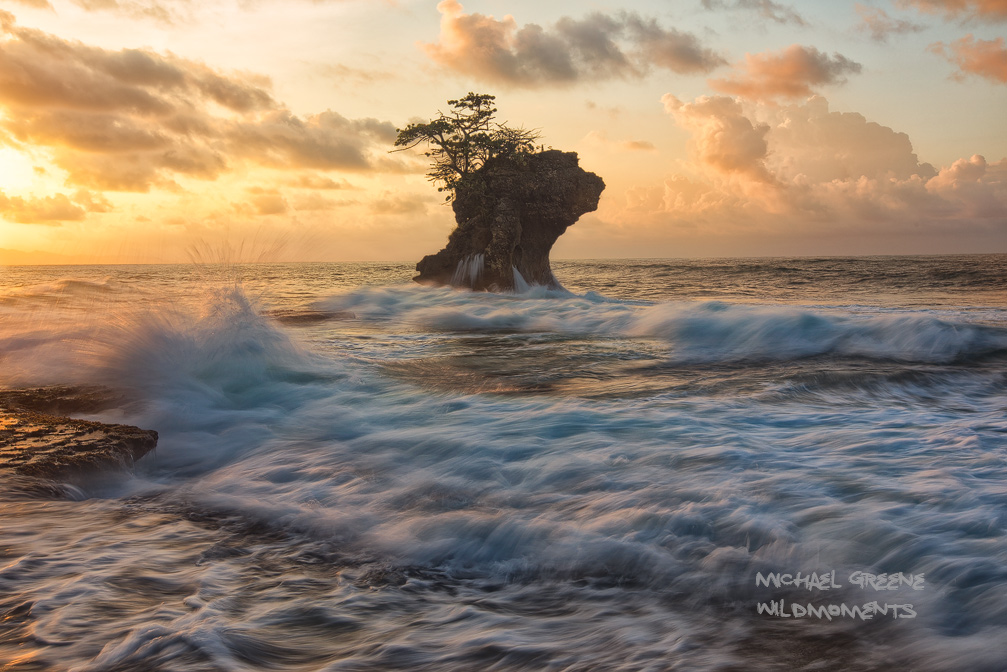 The stoic profile of a sea stack contrasts with the fading light of dusk amid a turbulent Caribbean surf and colorful evening...