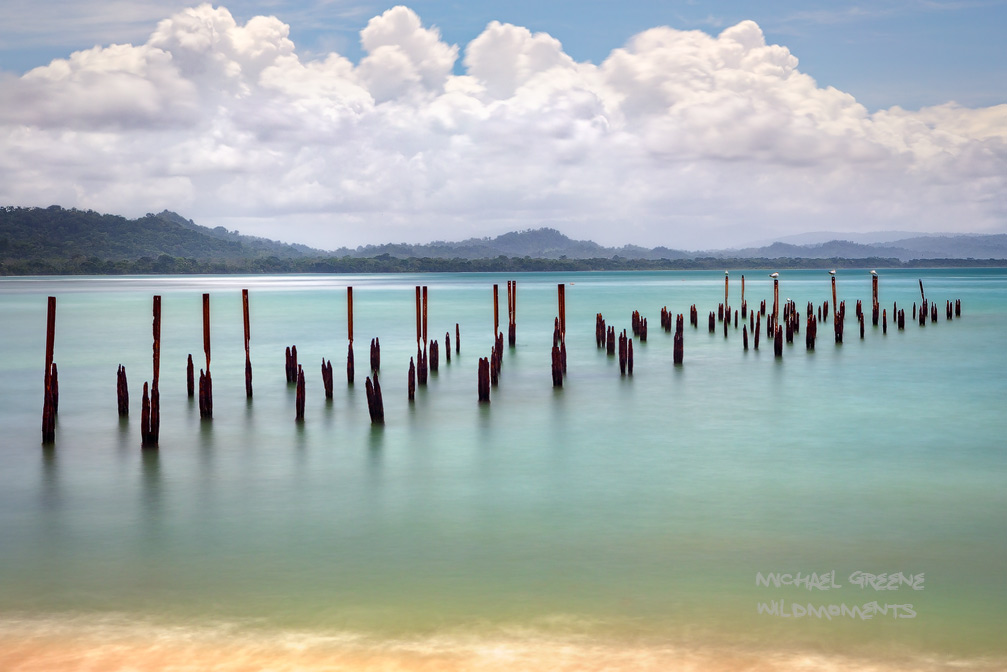 A time lapse photo of an old pier in the central portion of the beach hike at Cahuita National Park. This park is located in...