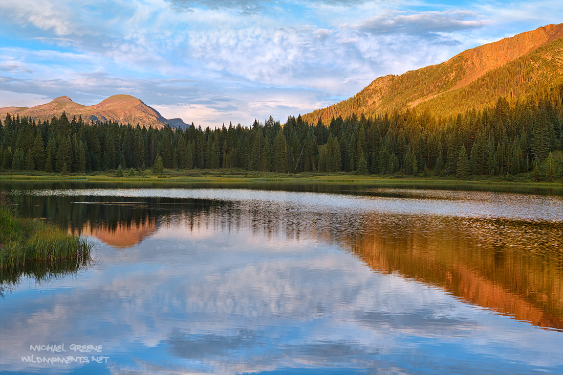 A quiet, sombre sunset reflects splendid light on Andrew's Lake near Molass Pass as storms through the nearby Weminuche Wilderness...