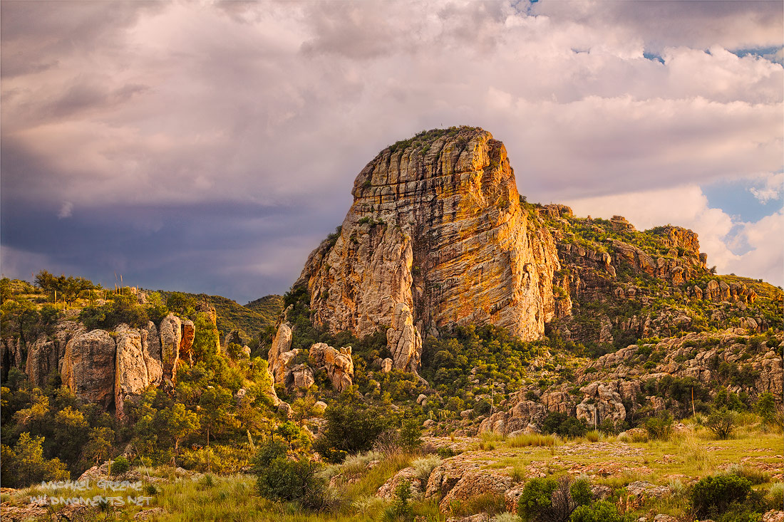 Monsoon light at sunset reflecting on a striking rock monument as seen from Ruby Road near Nogales, Arizona and the international...