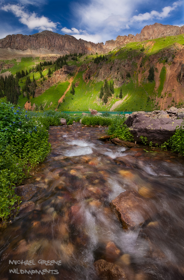 Lower Blue Lake during peak wildflower season as seen from a tributary on a partly cloudy day. Find this lake near the town of...