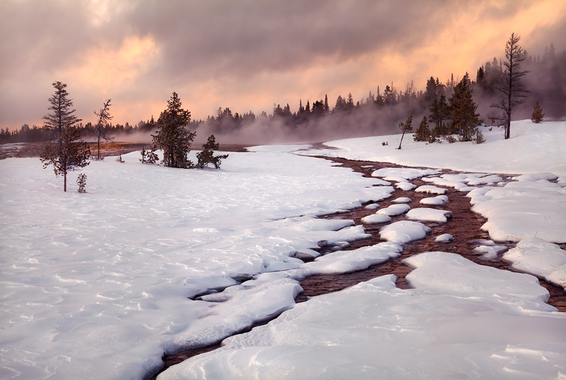 A heavy winter snowstorm dissipates at sunset in the frozen tundra of Upper Geyser Basin. While this area ranks asone of...