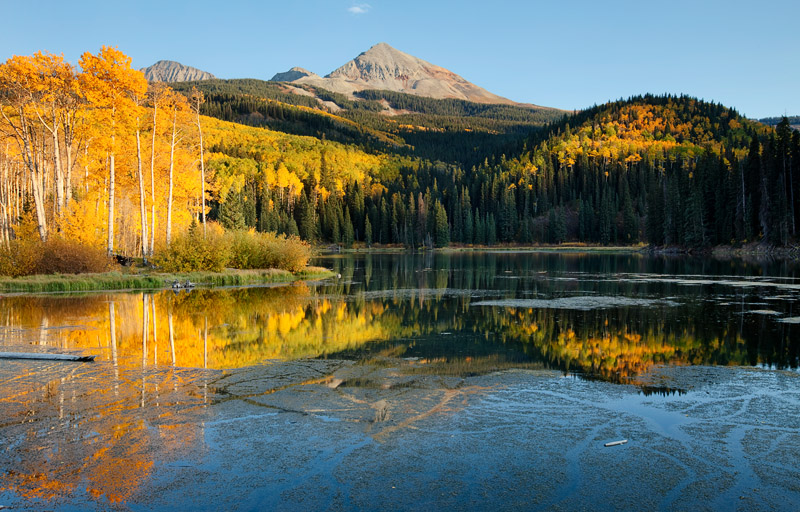 A profusion of fall colors accented by stillness, blue skies, and warm light on aquiet evening at Woods Lake near Telluride...