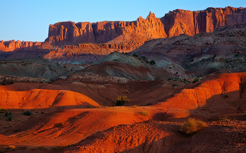 The criss crossing rays of first lightin Capitol Reef NP make itsNavajo Sandstone cliffsglow in splendor.&nbsp...
