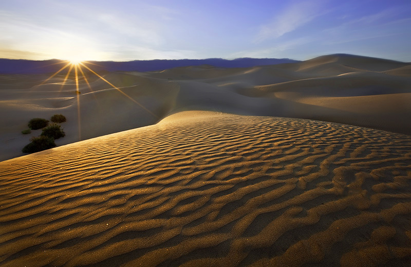 Sunbeams kiss the golden dunes of Mesquite Flats as another pleasant, sunny day in Death Valley comes to a close.