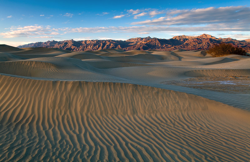 Late afternoon sunlight illuminates the flowing dunes of Mesquite Flatsand cloaks the Grapevine Mountains as clouds...