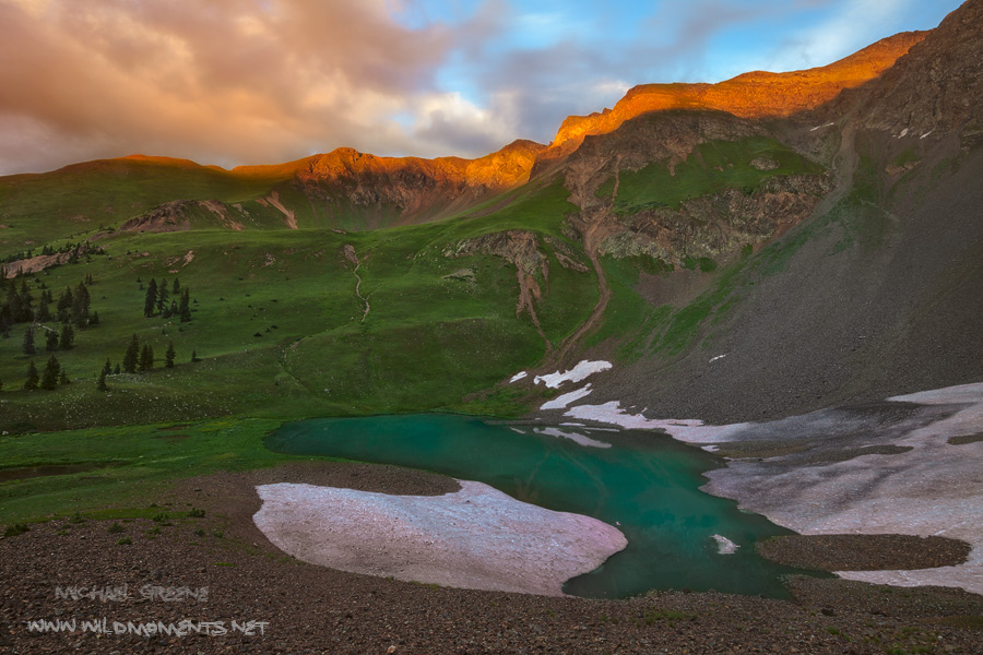 A unnamed tarn accentuates the beauty of a dramatic sunset during the final moments of evening light in the San Juan Mountains...