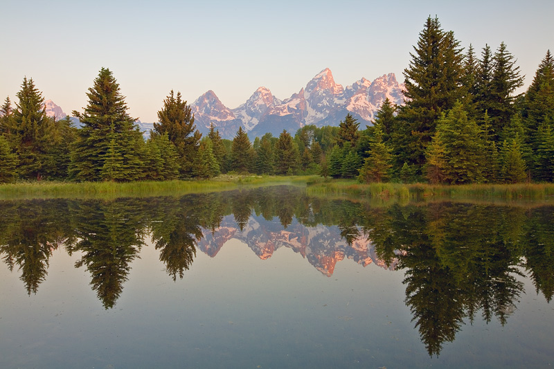 The soft light of sunrise illuminates the Teton peaks still covered in snow above 8500 feet reflected in the launching waters...