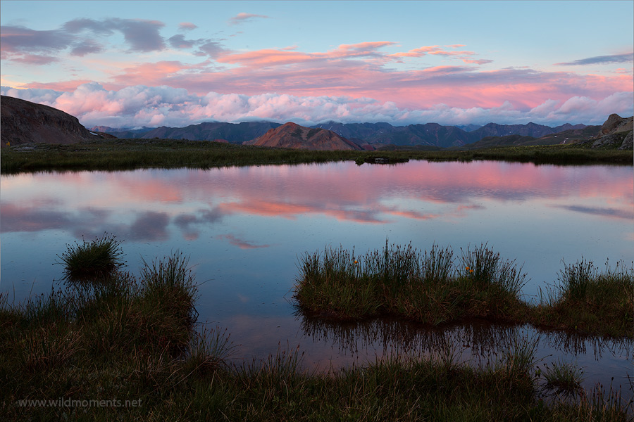 A high altitude tarn reflects the pink colors of sunset after a day of heavy, summer storms near Porphyry Basin.