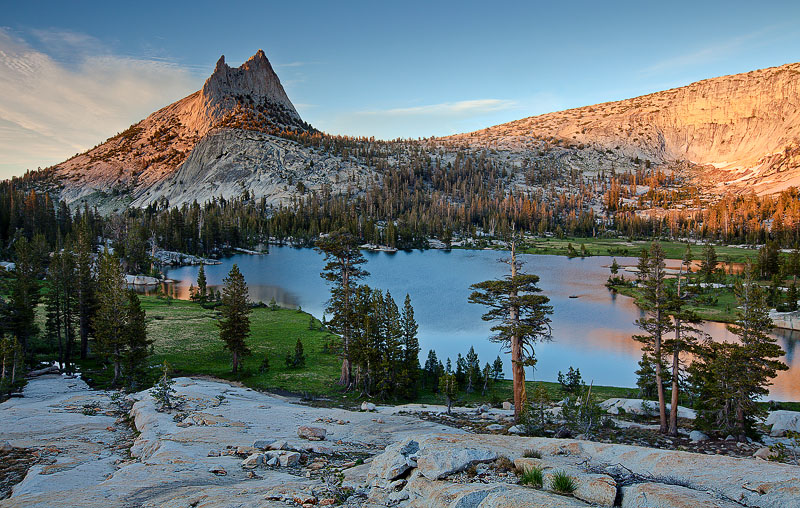 The golden glowof sunsetdapples briefly on the high crests of Cathedral Peak (10,991 ft)and in the waters of...